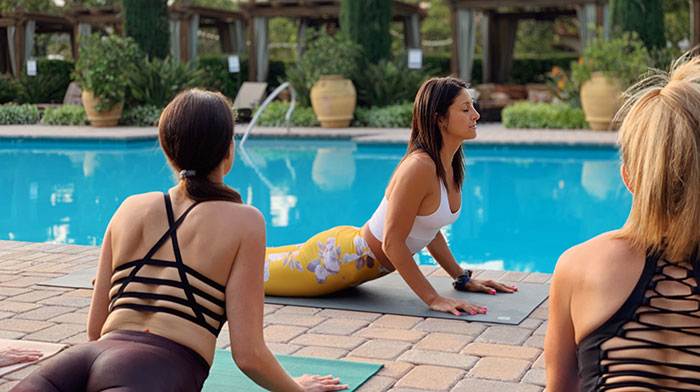 Girls doing Yoga by Pool
